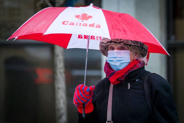 An elderly woman wears a disposable mask under an umbrella in Kingston, Ont., on Dec. 4, 2020. Many seniors...