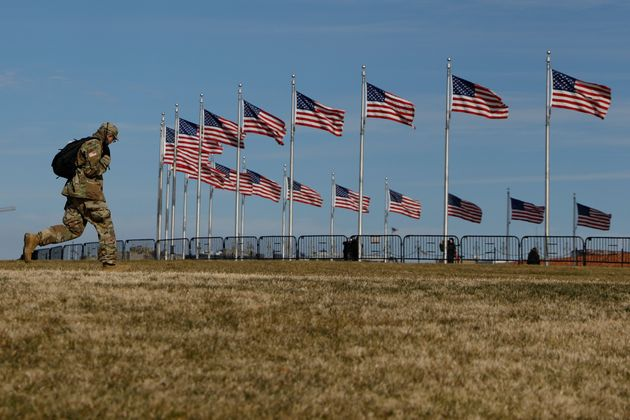 A National Guardsman walks past flags on the National Mall, four days after the inauguration of President...