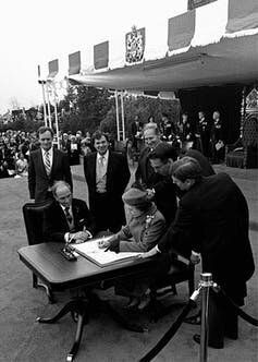 Queen Elizabeth signs Canada's constitutional proclamation in Ottawa on April 17, 1982, as Prime Minister Pierre Trudeau and other government officials look on. The patriation of the Constitution maintained the position of Governor General as the Queen's representative in Canada.