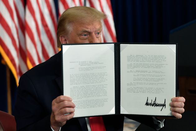 President Donald Trump signs an executive order during a news conference at the Trump National Golf Club...