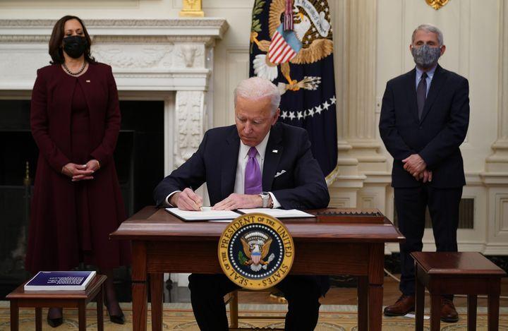 President Joe Biden signs executive orders on Jan. 21 as part of the COVID-19 response as Vice President Kamala Harris (left)