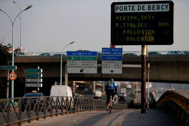 Un cycliste passe devant un panneau routier sur lequel est inscrit