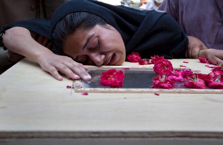 Una mujer llora sobre una tumba e un ser querido.