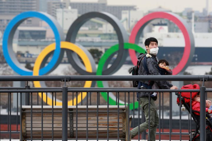 People wearing face masks to protect against the spread of the coronavirus walk on the Odaiba waterfront as Olympic rings are