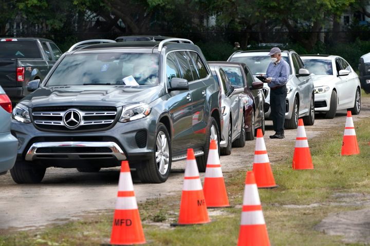 People in their vehicles are checked in at a drive-thru COVID-19 vaccination site at Marlins Park on Thursday in Miami.