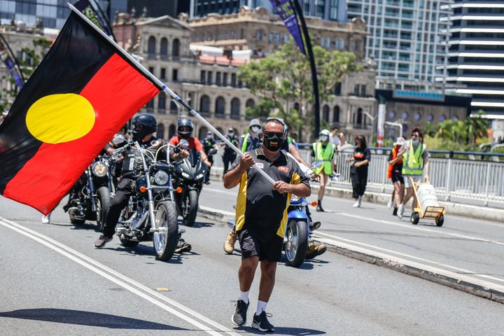 A protester waves the Aboriginal Flag across Victoria Bridge during the march. Crowds of people gathered in Brisbane, Queensland to protest against the Australia public holiday, which is a date synonymous with the beginning of many decades of persecution of Indigenous Australian people by the British colonialists.