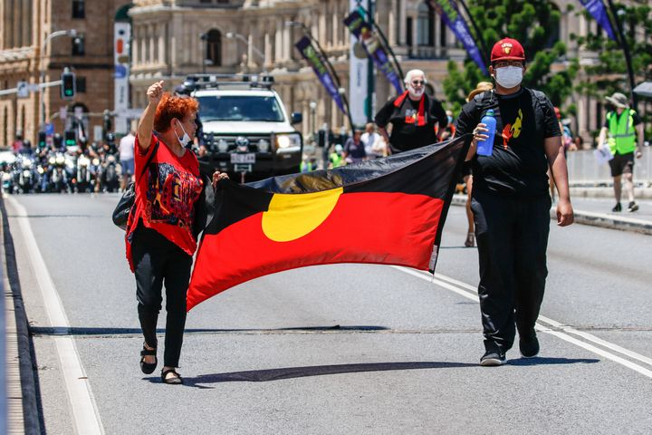 Protesters hold the Aboriginal Flag across Victoria Bridge during the rally.