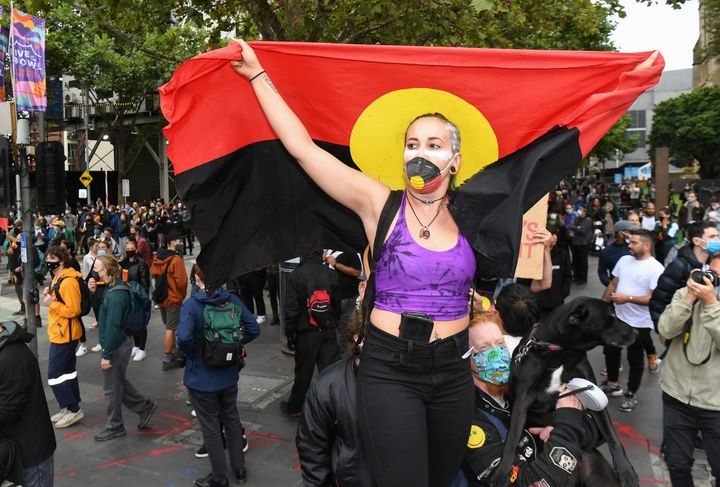 People hold placards as thousands of people attend an Australia Day protest in Melbourne in January 26, 2021.