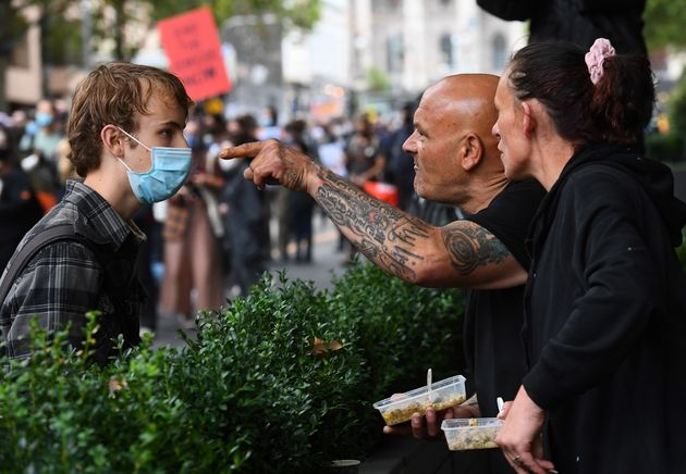 A couple (R) confront a protester as thousands of people attend an Australia Day protest in Melbourne in January 26, 2021.