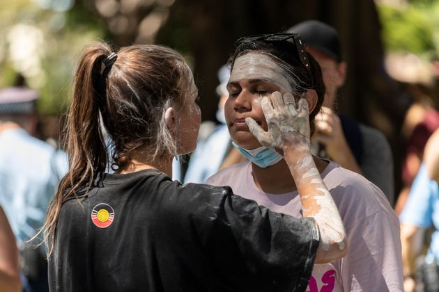 Vanessa Turnbull-Roberts (L) applies face paint to a fellow protestor during the Invasion Day rally on January 26, 2021 in Sydney, Australia.