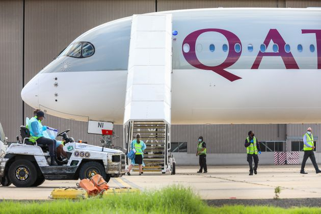 Biosecurity and airport staff in PPE and masks surround a chartered flight at Melbourne carrying players...