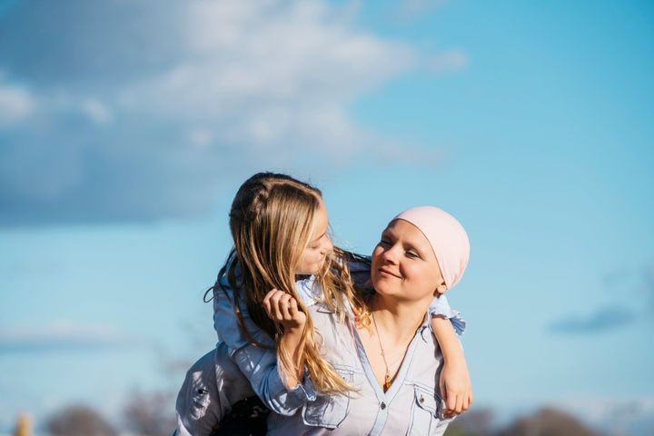 A woman with cancer is next to her daughter. A girl is hugging a woman happy