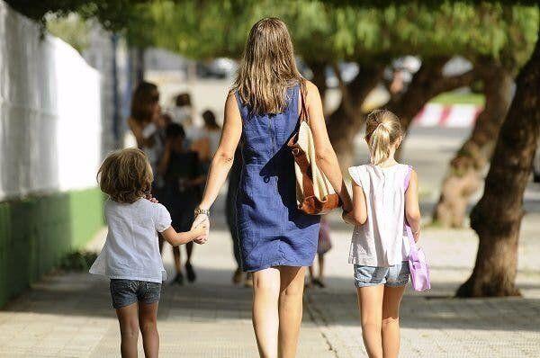 Una madre pasea con sus hijos.