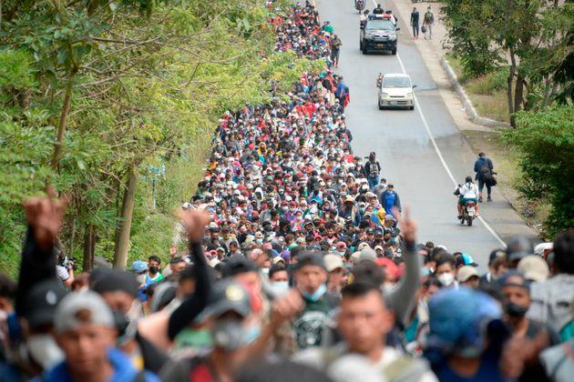 TOPSHOT - Honduran migrants, part of a caravan heading to the United States, walk along a road in Camotan,...
