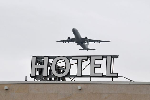 An airplane is seen flying over a hotel at Heathrow Airport in west
