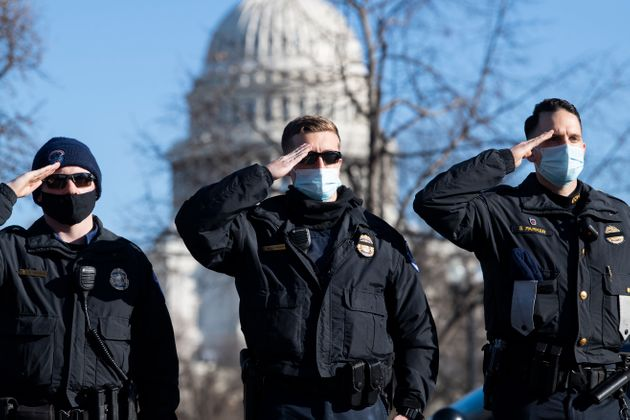 U.S. Capitol Police officers salute as the hearse carrying the body of their colleague, Officer Brian Sicknick, passes by in Washington on Jan. 10. Sicknick, 42, died from injuries suffered in the Jan. 6 attack on the U.S. Capitol that followed a rally headlined by then-President Donald Trump.