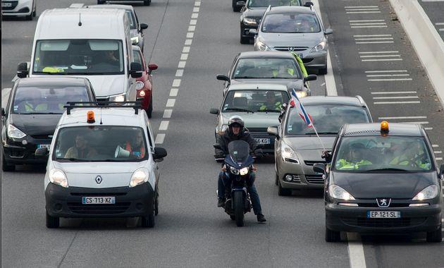 Un motard circule entre deux files de voitures, en pleine manifestation Gilets-Jaunes à Rennes...