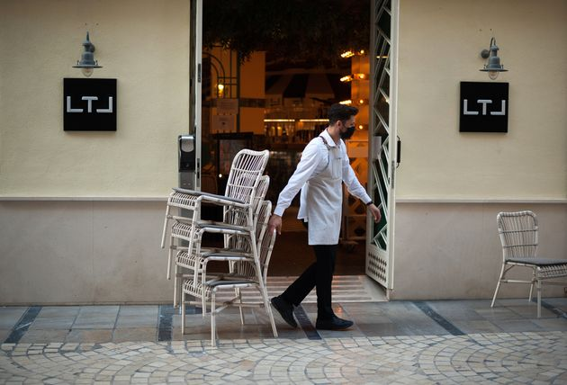 Un camarero de un bar de Málaga guarda las sillas tras el cierre
