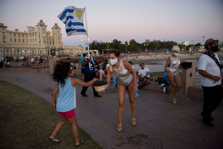 A girl hands over a coin to a Candombe artist performing at the Rambla of Montevideo, Uruguay, on Jan. 23, 2021. Countries wi