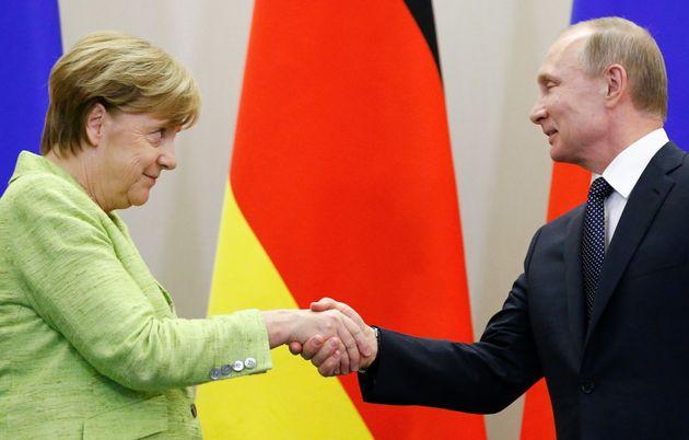 Vladimir Putin saluda a Angela Merkel durante un encuentro en 2017, en su casa de verano
