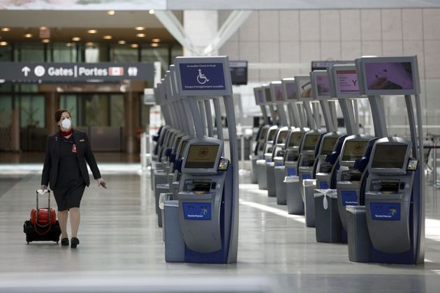 A flight attendant walks through Toronto Pearson International Airport in Mississauga, Ont., on April...