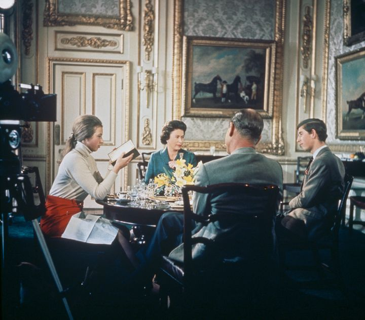 """Queen Elizabeth lunches with Prince Philip (center), Princess Anne and Prince Charles at Windsor Castle in 1969. A camera (left) is set up to film for Richard Cawston's BBC documentary """"Royal Family."""""""