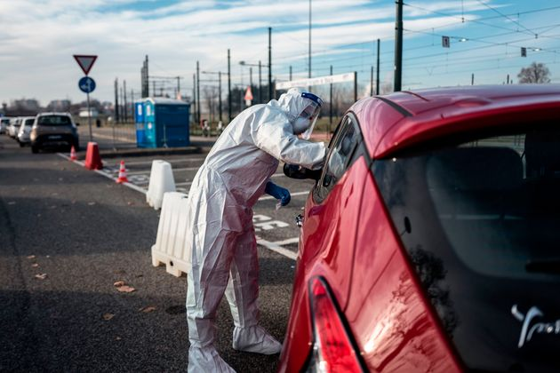 A military medical worker collects on January 12, 2021 a swab sample from a person going through a drive-in...