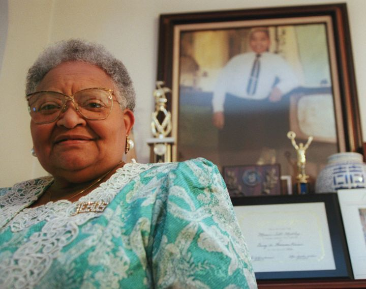 Mamie Till-Mobley, who died in 2003, poses before a portrait of her slain son.