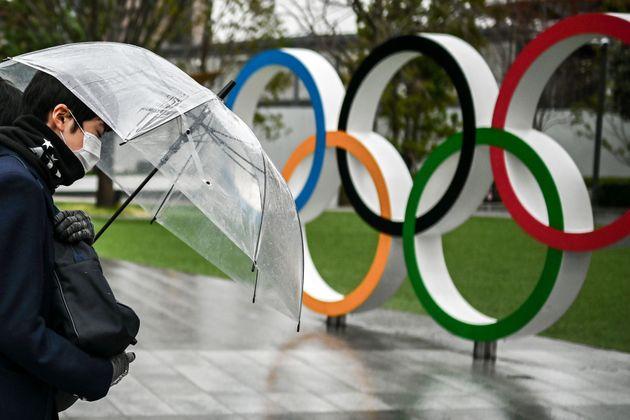 Un ciudadano japones posa serio junto a los aros olímpicos que decoran