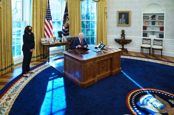 President Joe Biden, with Vice President Kamala Harris, signs executive orders on health care in the Oval Office on Thursday.