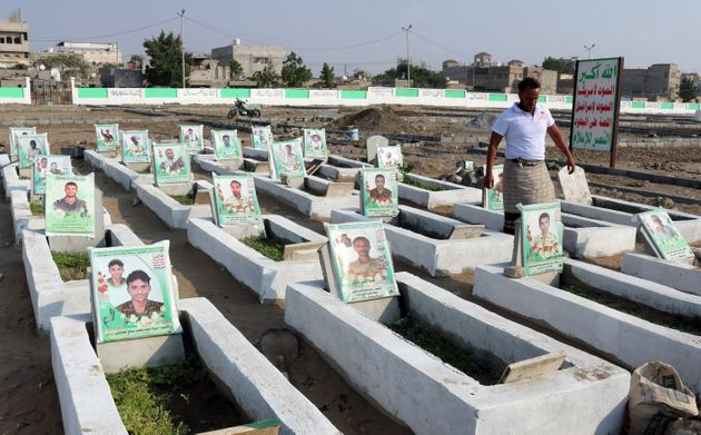 A Yemeni men walks among graves of men said to be killed in the countrys ongoing war, at a cemetery in...