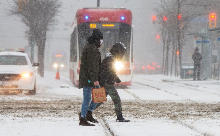People wearing face masks cross a street during a snowfall in Toronto, Jan. 26, 2021.