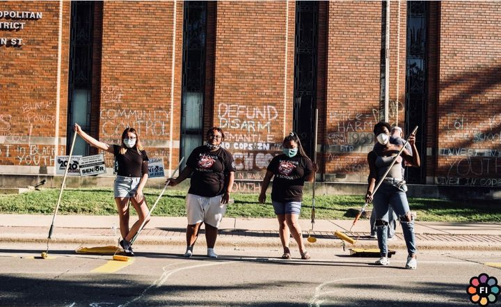 "Adams (second from left) and members of the Freedom Youth Squad painted ""Police free schools"" on the road in fron"
