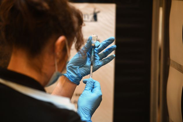 A healthcare professional draws up a dose of Covid-19 vaccine to be administered at a vaccination
