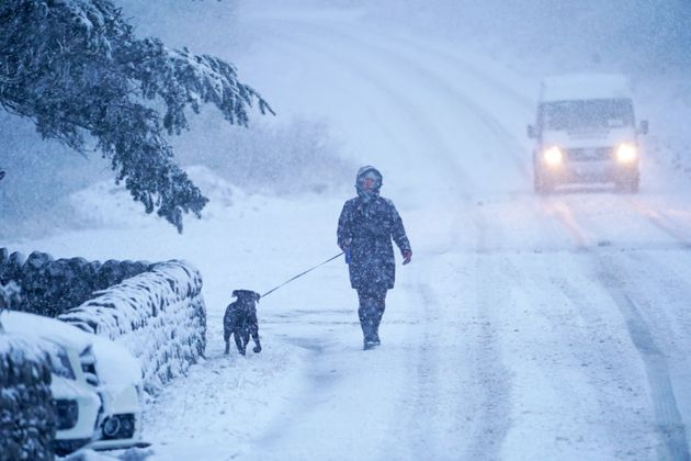 A dog walker and a van make their way along a snow covered road in Northumberland, as parts of the UK...