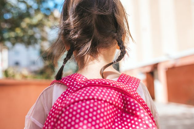 Closeup rear view portrait of cute little girl preschooler posing outdoor with pink backpack against blurred building. Happy kid toodler girl walking after learning school lessons. People, education