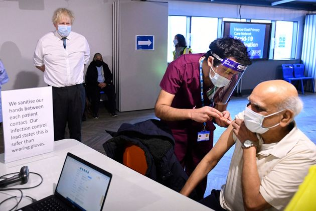 Boris Johnson watches a patient receiving a dose of the Oxford/Astrazeneca coronavirus vaccine, during...