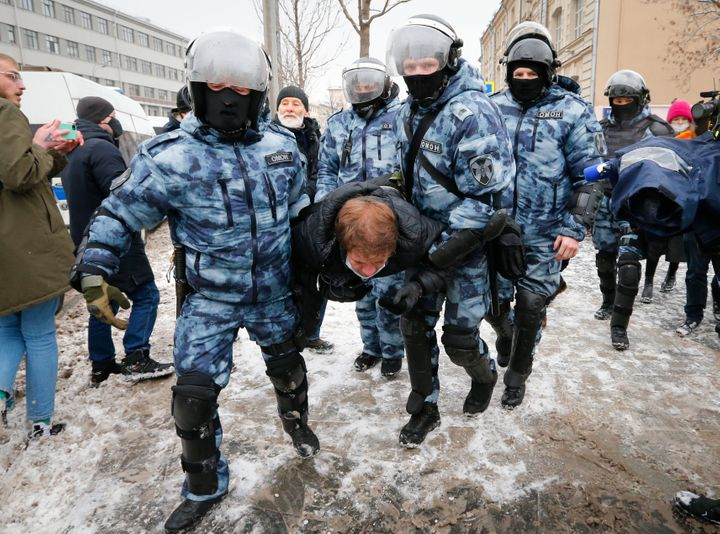 Police officers detain a man during a protest against the jailing of opposition leader Alexei Navalny in Moscow, Russia, on S