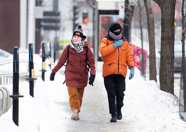 People wear face masks as they brave the cold weather in Montreal on