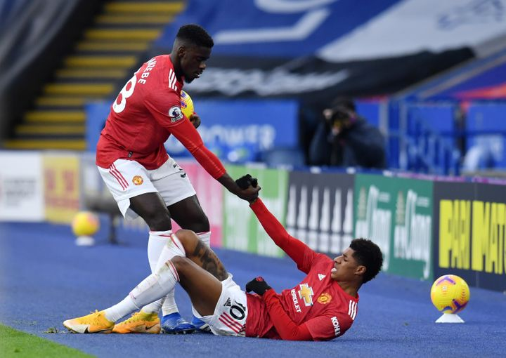 Axel Tuanzebe of Manchester United helps up teammate Marcus Rashford during a match on Dec. 26.