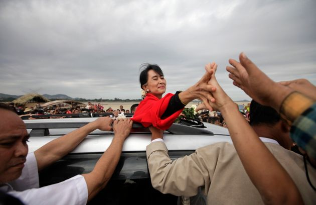 Myanmar pro-democracy leader Aung San Suu Kyi shakes hands with supporters after giving a speech in Monywa...