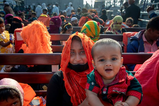 A Rohingya refugee woman with her son sits on a Bangladesh navy vessel will move to the Bhasan Char island...