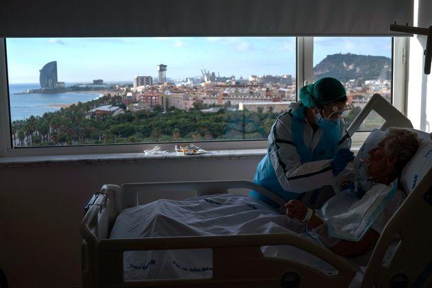 Ana Aguilar, una auxiliar de clínica, alimenta a una paciente de coronavirus en el Hospital del Mar de Barcelona, el pasado noviembre.