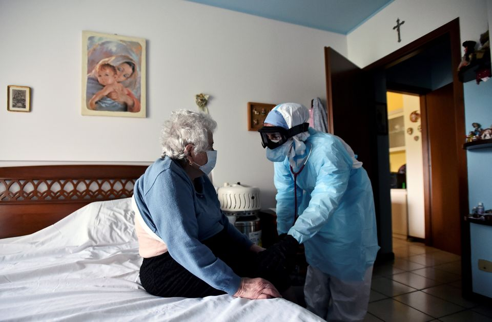A doctor in protective suit visits a person suffering from the coronavirus disease (COVID-19) at her...