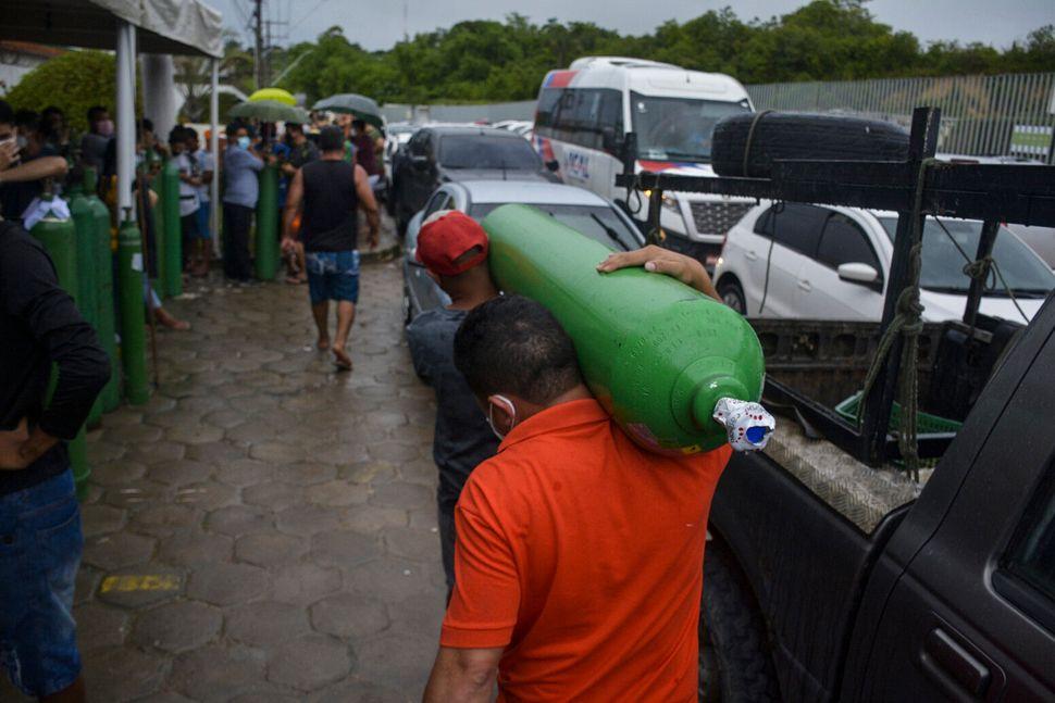 Parenti di malati Covid-19 tornano a casa dopo ore d'attesa per riempire le bombole d'ossigeno a Manaus,...