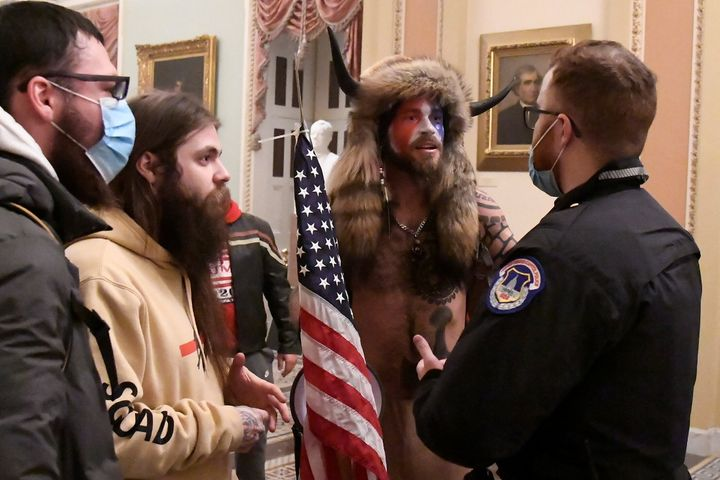 Jacob Anthony Chansley, also known as Jake Angeli, of Arizona speaks with a U.S. Capitol Police officer after supporters of t