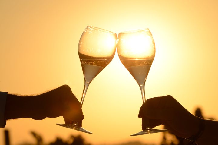 toasting with sparkling wine at sunset