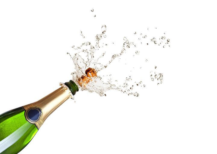 detail of popping champagne on black background