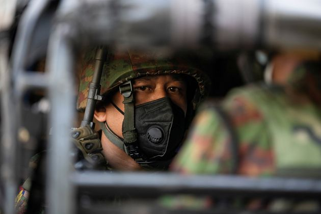 Myanmar soldier sits inside a military vehicle in front of a Hindu temple in the downtown area, in Yangon,...