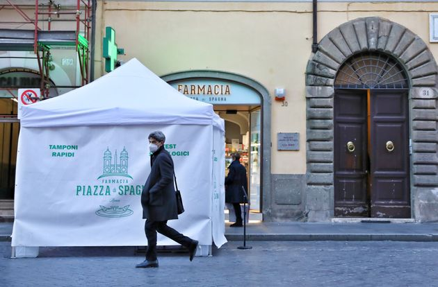 ROME, Jan. 27, 2021 -- A man wearing a face mask walks past a rapid test for COVID-19 point in Rome,...
